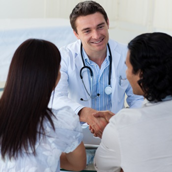 Smiling doctor explaining diagnosis to a couple during a visit